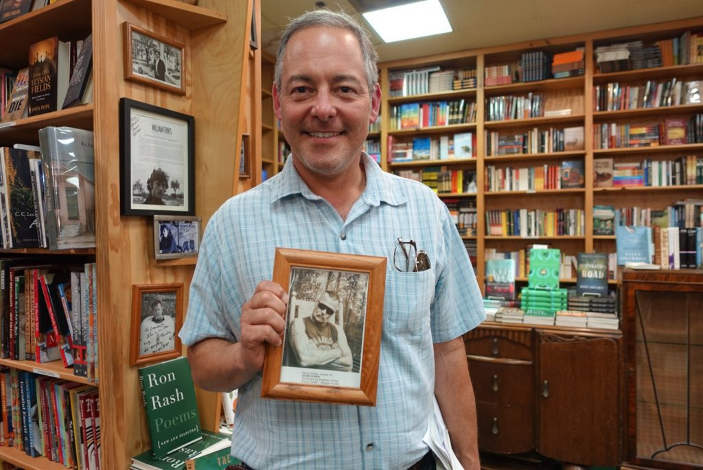 Ted Geltner holding the framed photo of Harry Crews that hangs on the wall at Lemuria Books