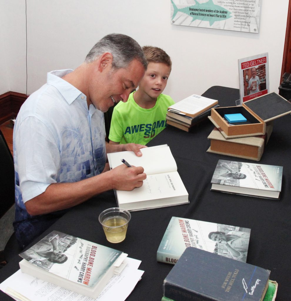 Luke Geltner, 9, at his dad's side as he signs books